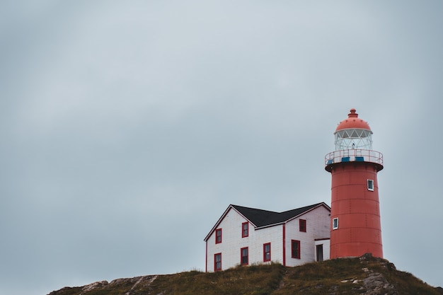 Red lighthouse beside house