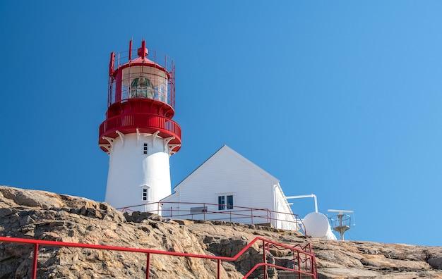 青い海の岩の上の白い家の近くの赤い灯台