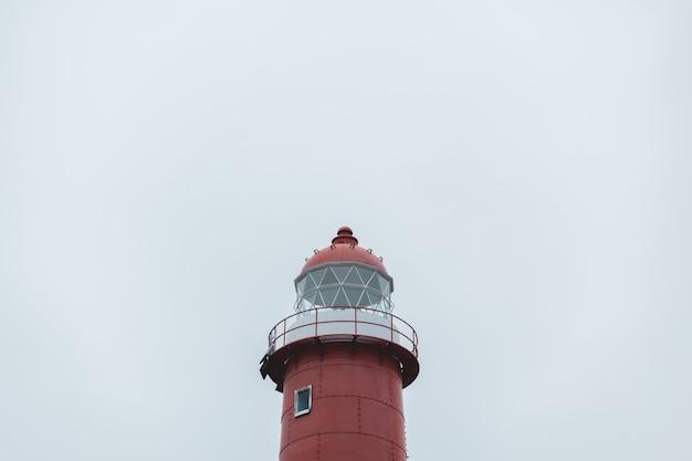 Красный маяк над облачным небом