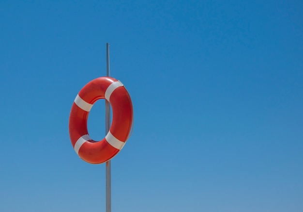 Red liifebuoy on the pole on blue sky background