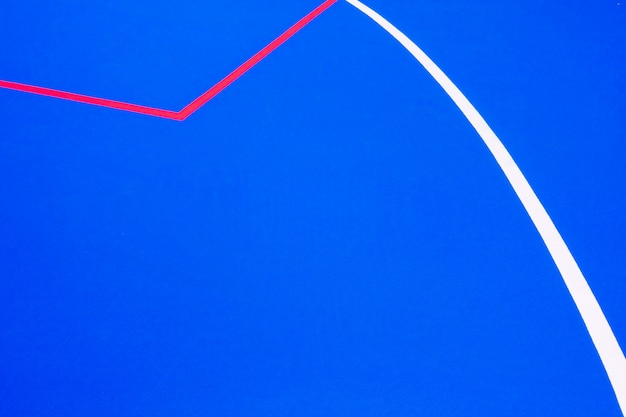 Red lines crossing a floor painted blue of intense color to use as a minimalist design background.