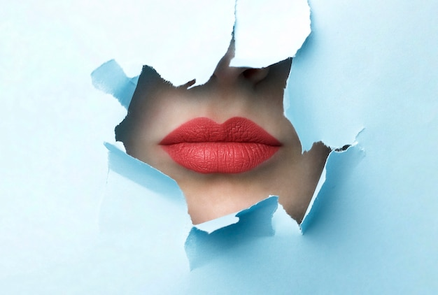 Red lips and blue torn paper background