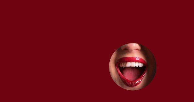 Red lips and shiny smile through hole in red paper background