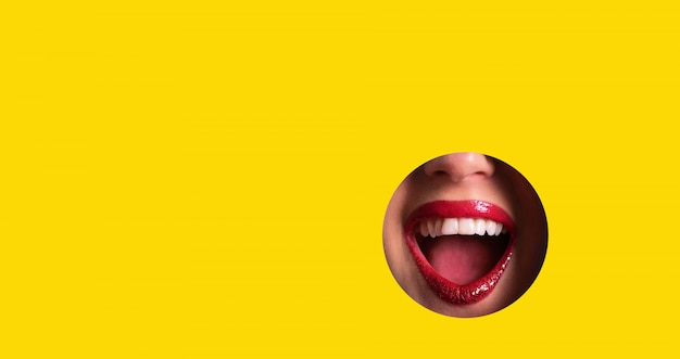 Red lips and shiny smile through hole in yellow paper background
