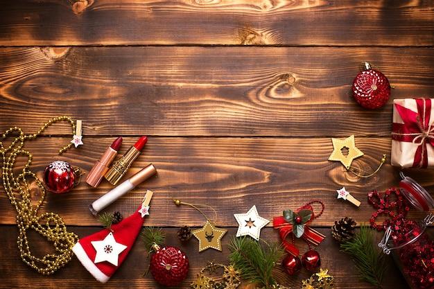 Красная помада и блеск для губ и веки на деревянном фоне в рождественском декоре. праздничный макияж на новый год, подарок, шоппинг, женские желания. место для текста, плоская планировка