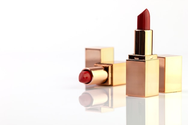 Red lipstick in golden box on white background.