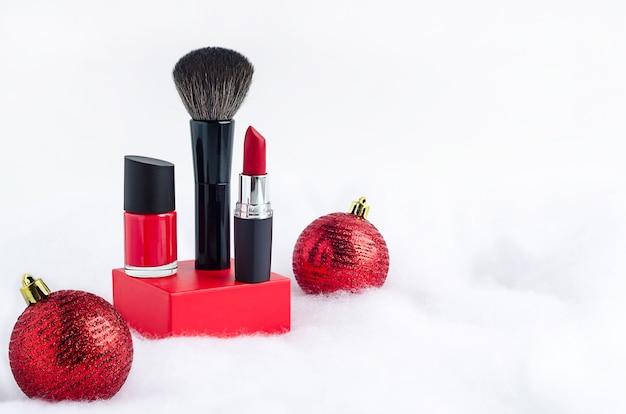 赤い口紅、マニキュア、雪の上の表彰台にブラシ。流行の高級化粧品は美容製品を構成します。新年の女性へのクリスマスプレゼント。