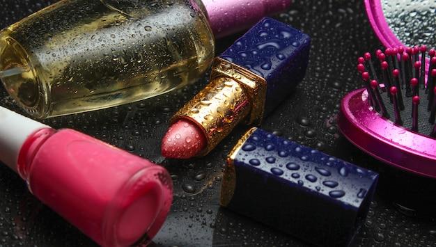 Красная помада, флакон духов, лак для ногтей, зеркальная расческа с каплями воды на темно-черном фоне. красота и мода.