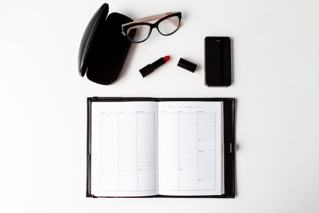Red lipstick phone glasses and notebook over white background