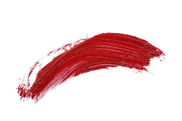 白い背景に分離された赤い口紅の汚れの汚れ