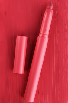 Red lipstick tube texture, lip gloss close up. beauty industry concept.