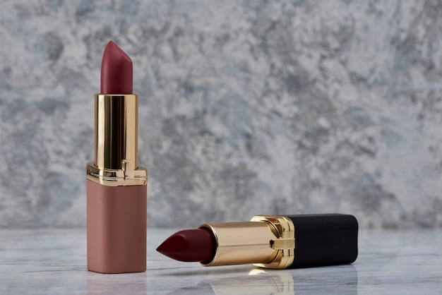 Red lipstick with black and pink on a marble surface with the caps thrown to the side