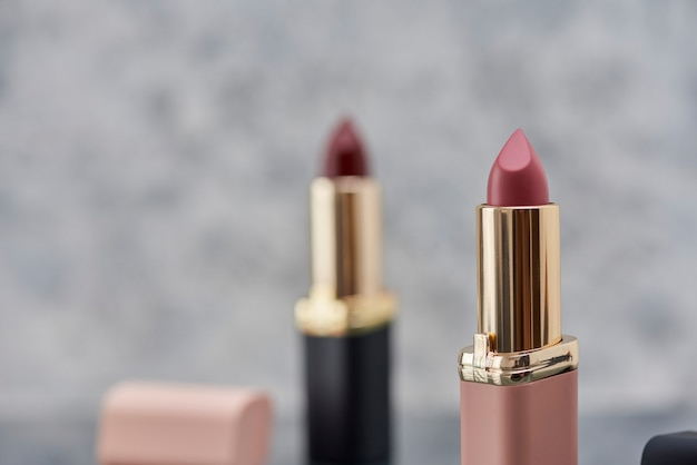 Red lipstick with black and pink on a marble surface with the lids thrown to the side