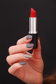 Red lipstick in a woman's hand