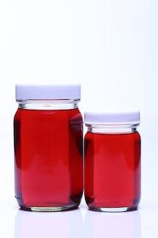 Red liquid in glass bottle white cap