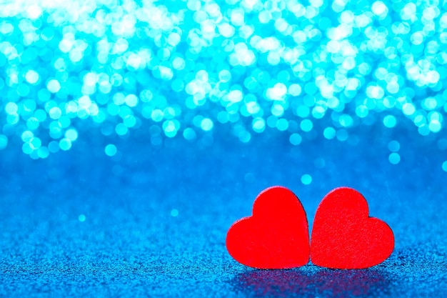 Красные маленькие декоративные сердечки на фоне голубого блеска с удивительными огнями боке.
