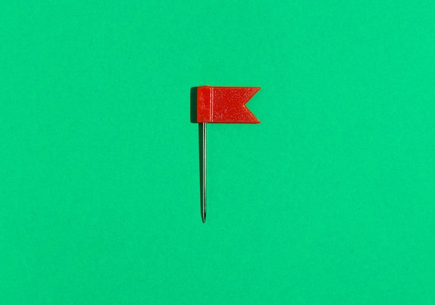Красная маленькая булавка флага на зеленом фоне. вид сверху.