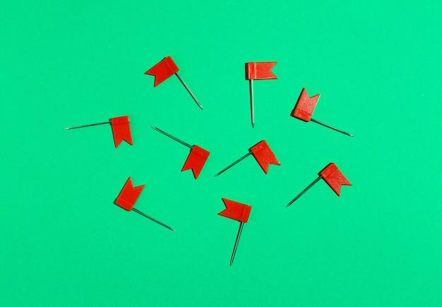 Красные маленькие булавки флага на зеленом фоне. вид сверху.