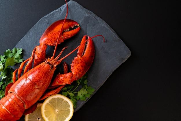 Red lobster with vegetable and lemon slices on black slate