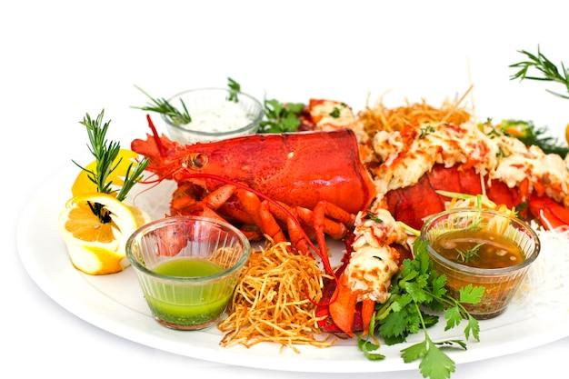白い皿に野菜と赤いロブスター。孤立した