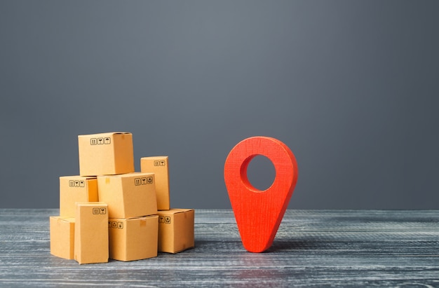 Red location pointer geolocation symbol and cardboard boxes