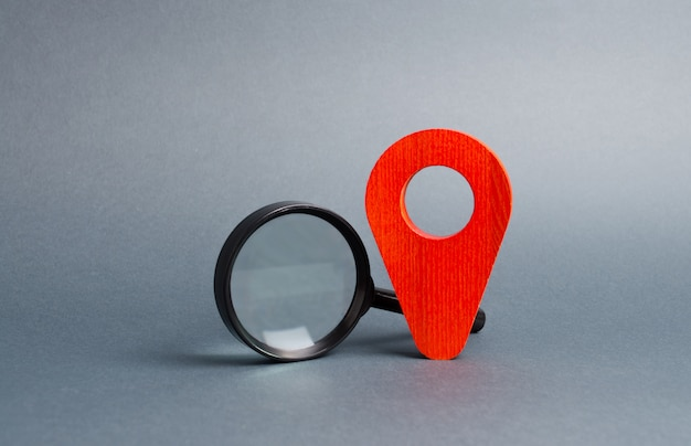 Red location pointer and a magnifying glass on a gray. tourism and travel
