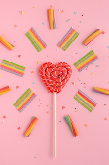 Red lollipop in shape of heart and colorful sweets on pink, flat lay