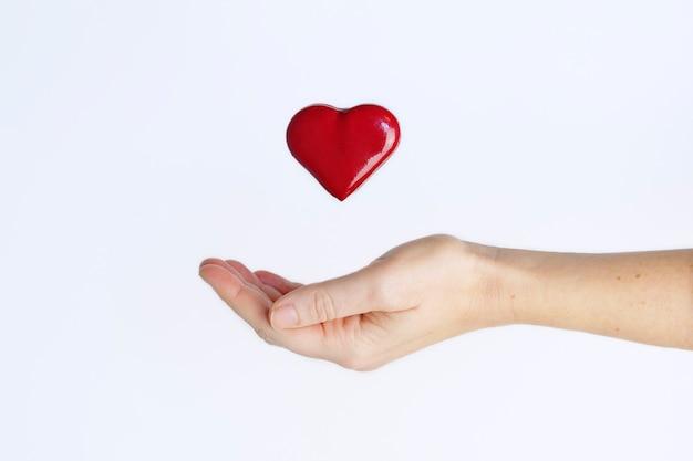 흰색 배경에 대해 뻗은 여성 손에 공중에 떠 있는 붉은 사랑 마음. 사랑 개념입니다.