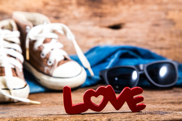 Red love lettering on jeans and sneakers on wooden background