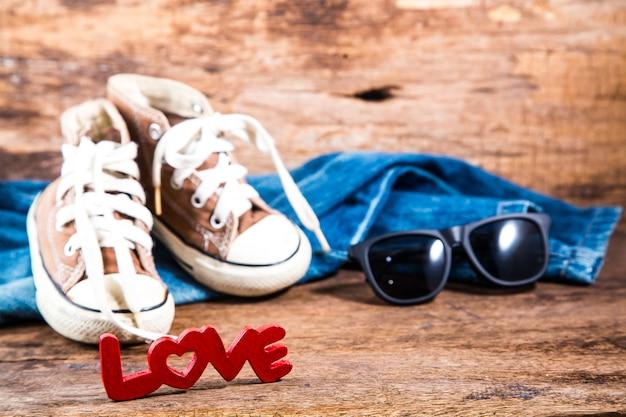 木製の背景にジーンズとスニーカーの赤い愛のレタリング