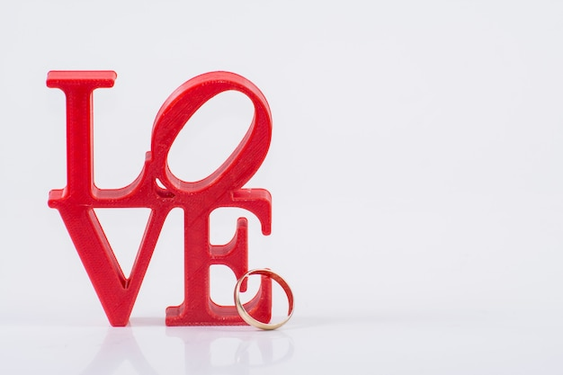 Red love letters on white background on the left wiht ring