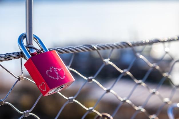 橋の金網に掛かっている赤い愛ロック