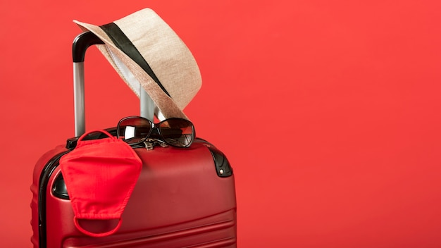 Red luggage with hat and copy-space