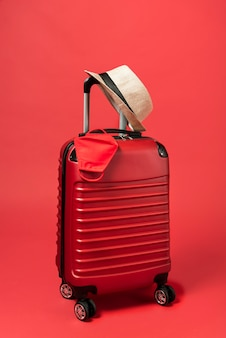 Red luggage with hat and mask