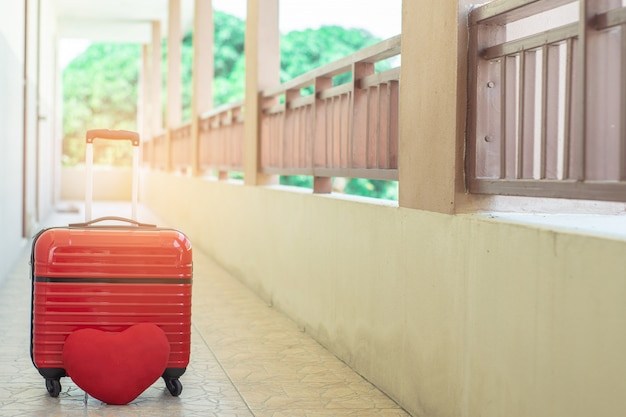 Red luggage with red heart on blurred for activity lifestyle outdoors