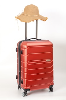 Red luggage with straw hat