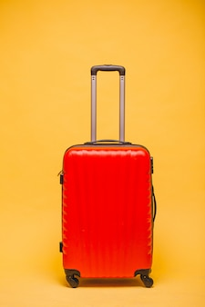 Red luggage on a yellow background isolated