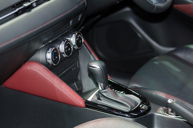 Red luxury car interior with steering wheel, shift lever and air condition and radio button