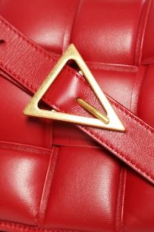 赤い高級ファッションバッグのクローズアップゴールドクラスプ