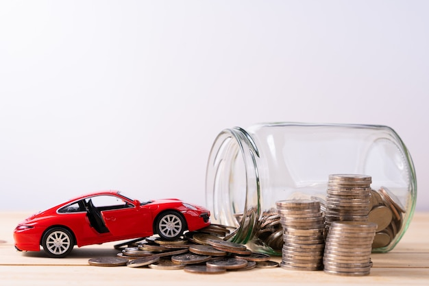 Red luxury toy car next to glass jar with coins on wooden table and white wall