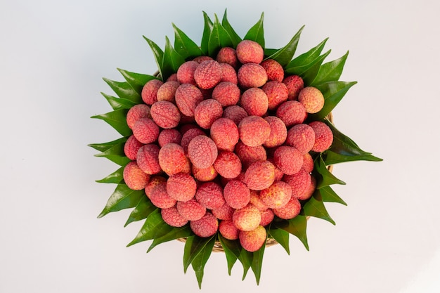 Red lychee fruit placed in a basket