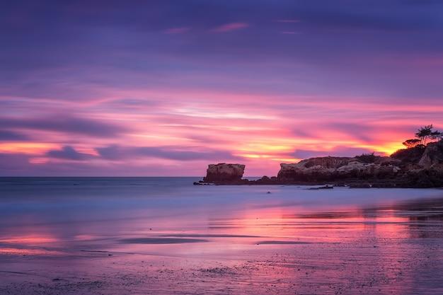 アルブフェイラのオウラのビーチに沈む赤い魔法の夕日。ポルトガルアルガルヴェ