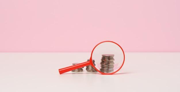 テーブルの上の赤い拡大鏡と白いコイン。所得成長の概念、投資の高い割合。新しい収入源、補助金を探す