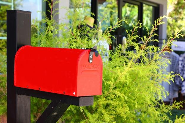 Красный почтовый ящик в передней части дерева и офисного здания