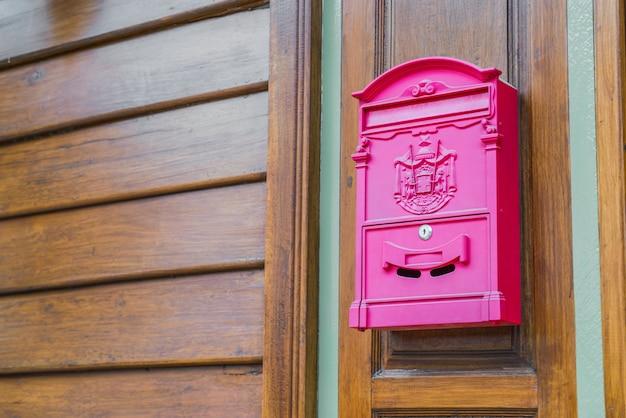 Cassetta postale rossa sulla parete di legno