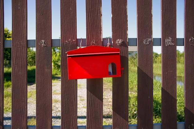 Красный почтовый ящик на коричневых воротах перед домом