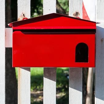 Красный почтовый ящик на белом заборе