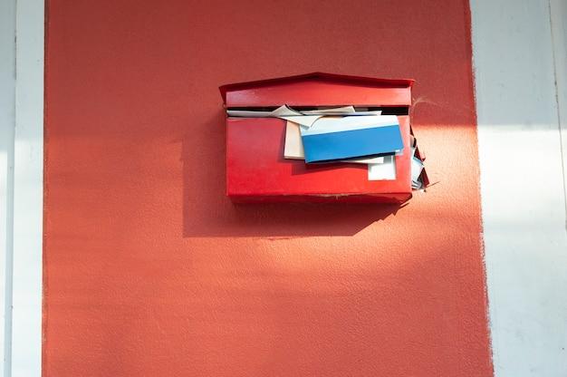 Красный почтовый ящик с переполненными документами, почтовый ящик давно не открывали, красные почтовые ящики на красных стенах