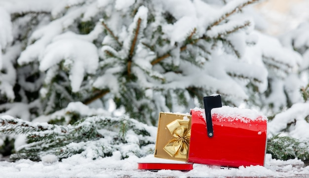 Red mailbox with gift box inside on wooden table in snow