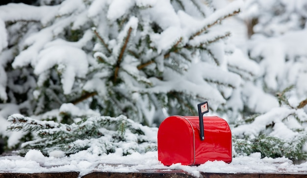 Red mailbox on wooden table in snow